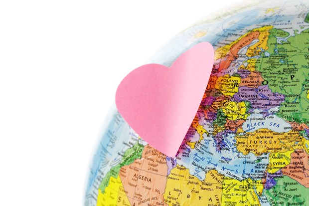 Earth globe and paper heart on white